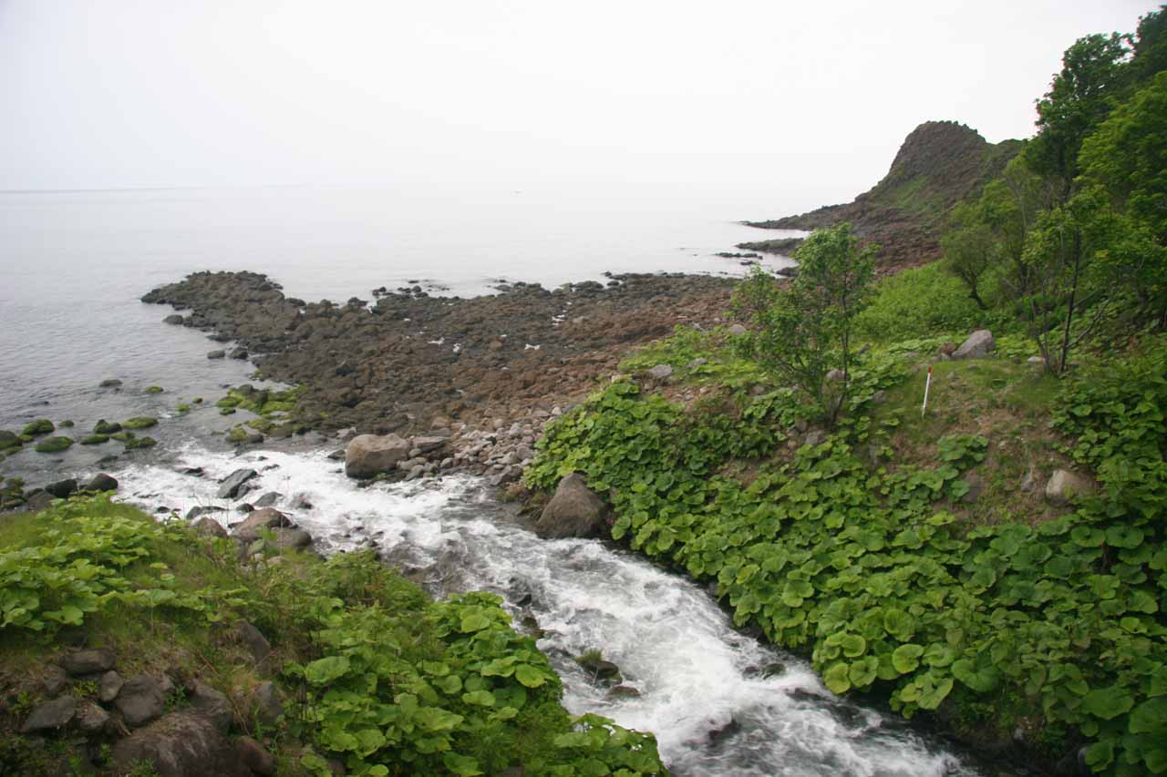 Looking at the outlet of the Oshinkoshin Waterfall as it joins the Sea of Okhotsk