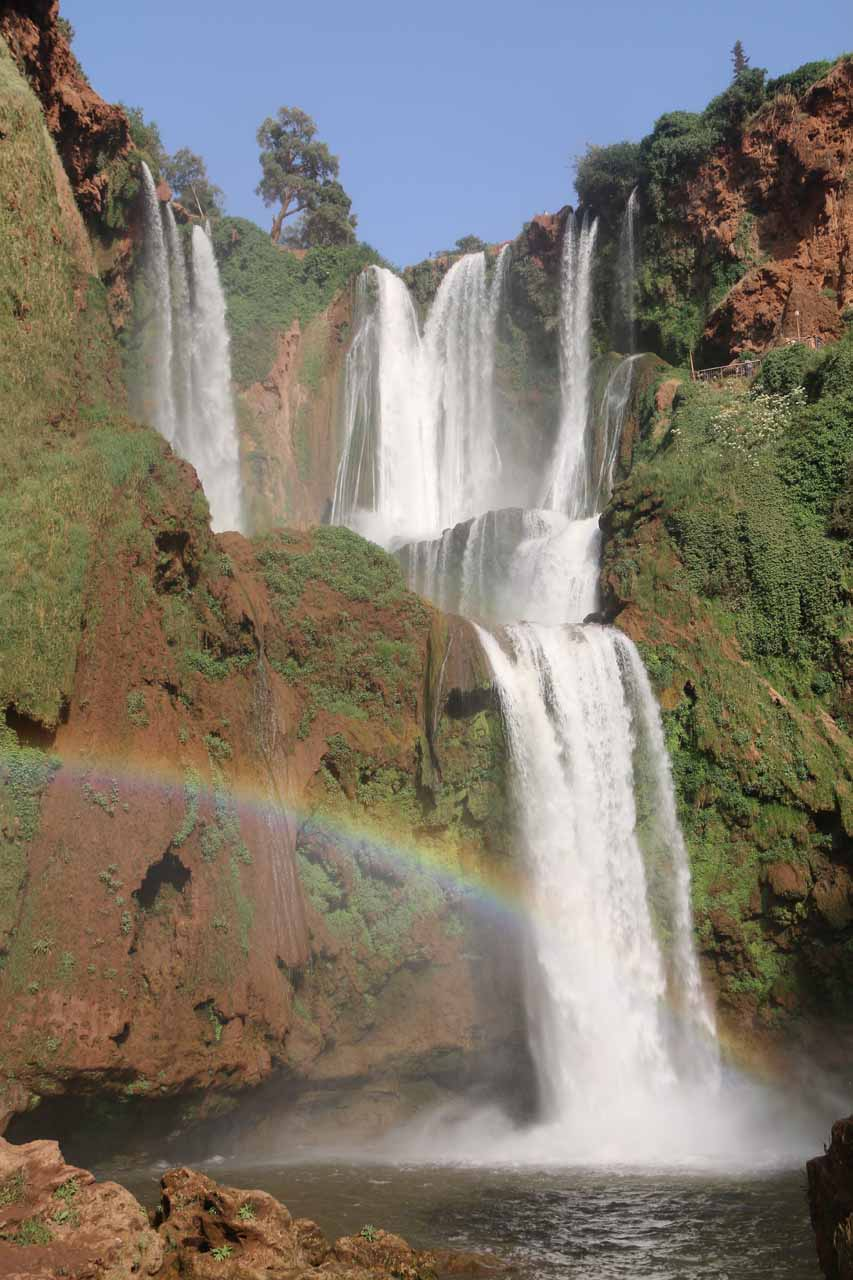 Frontal view of Cascades d'Ouzoud with a wide arcing rainbow right across it