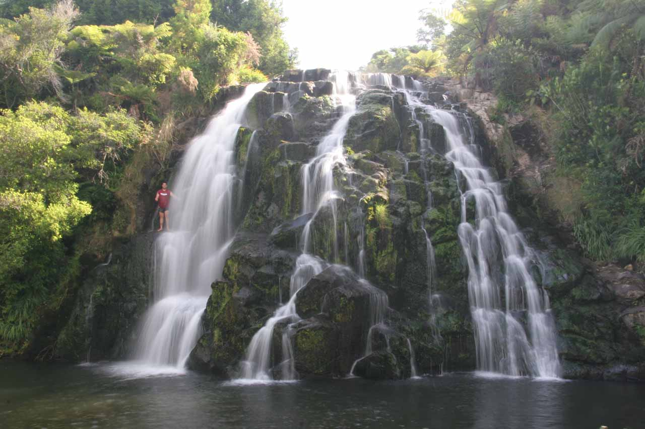 A closer look at Owharoa Falls with a Maori individual about to jump from a ledge in the middle of the falls
