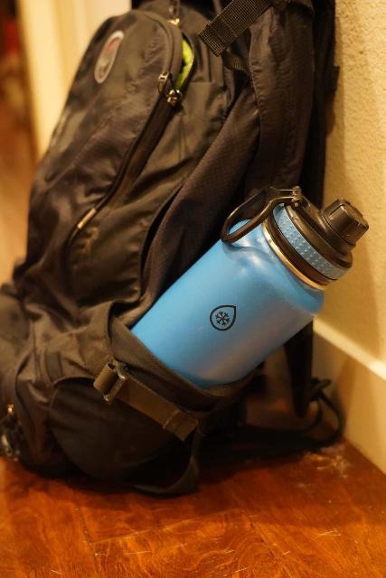 The tilting 32oz stainless steel bottle that's about to fall out of the Osprey Ozone 46 demonstrates how shallow its side pockets are