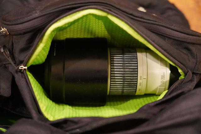 Looking inside the slash pocket of the Osprey Ozone 46 Travel Backpack, which easily fit a 70-200mm telephoto zoom lens with the lens hood on