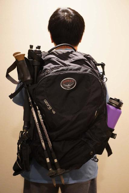 Using a combination of the side pockets and the compression strap to secure a tripod and trekking pole onto the Osprey Ozone 46 Travel Backpack, but this comes at the expense of sacrificing water bottle usage