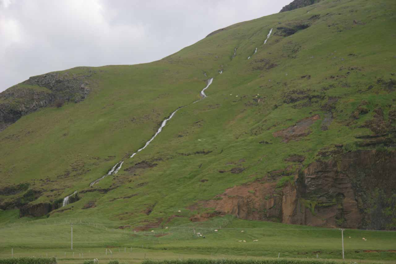 A waterfall sloping near Paradishellir with sheep grazing in the distance