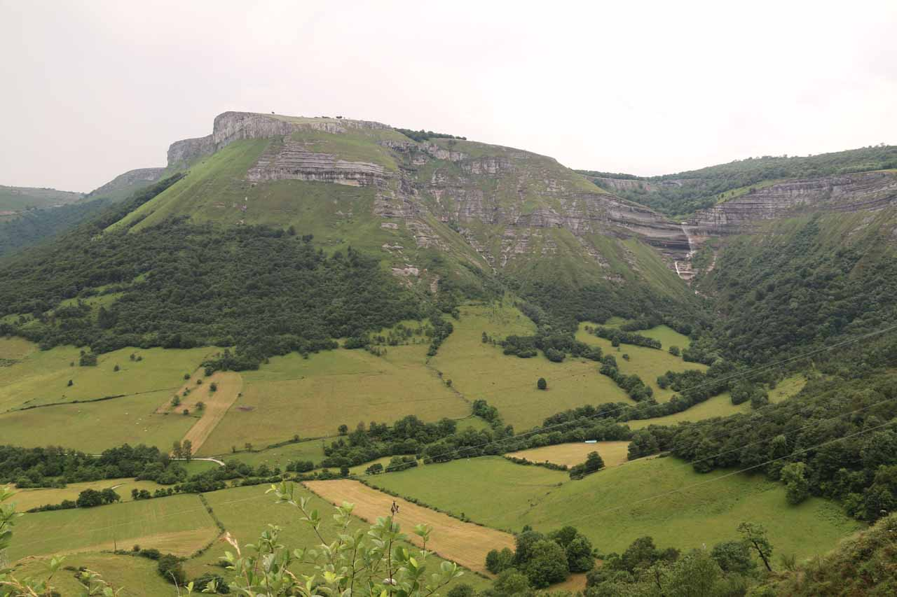 Contextual view of the butte-like mountain with the cliff-diving waterfall both backing a valley below