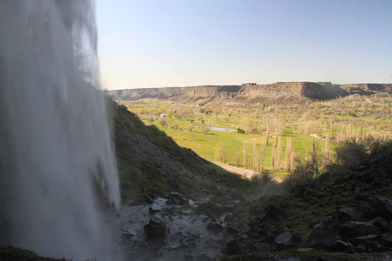 Looking out from behind Perrine Coulee Falls towards the Snake River Canyon and the greens of the Blue Lakes Country Club