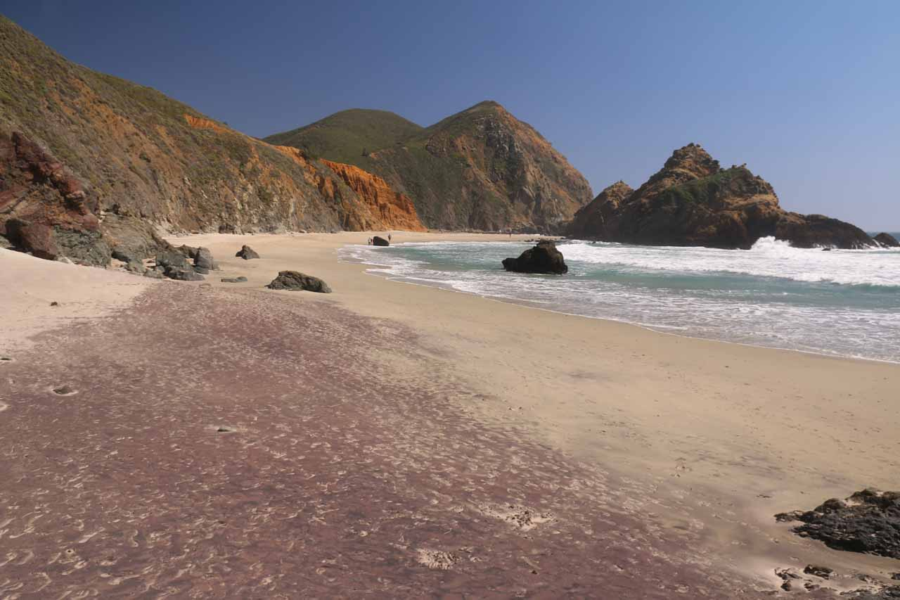 Colorful scene of purple sand fronting orange cliffs and blue skies all contrasting each other at Pfeiffer Beach