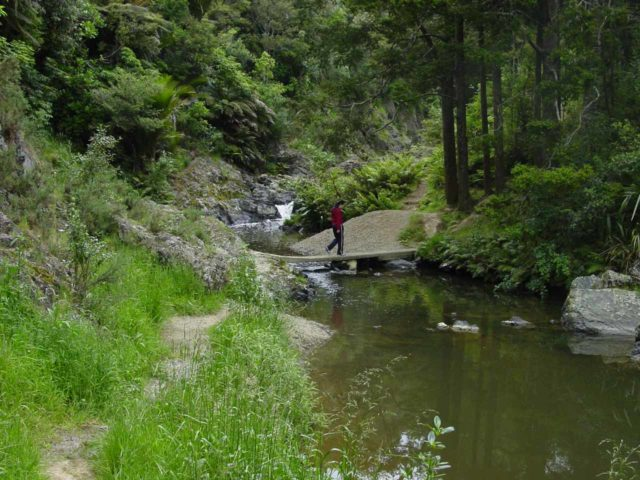 Piroa_Falls_006_11062004 - Julie crossing over a short concrete bridge traversing the Ahuroa River