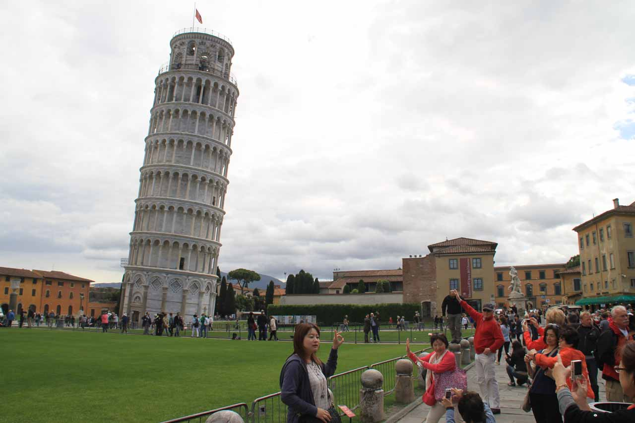 Many people pushing at the air trying to get their own fun shot of Pisa