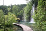 Plitvice_357_06012010 - Context of someone walking on the boardwalk fronting another one of the taller and attractive Plitvice Waterfalls of the Upper Lakes