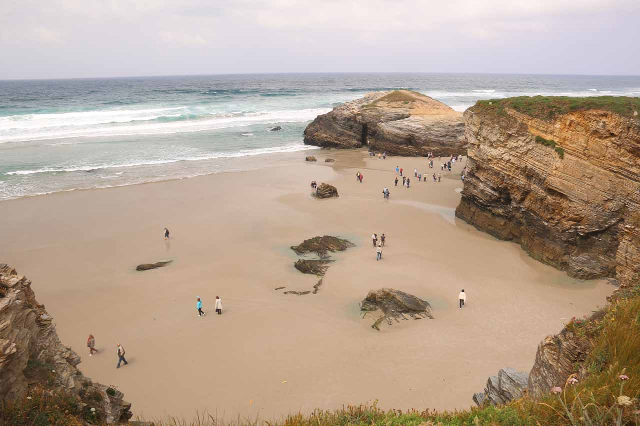 Another contextual look down at the people trying to walk across the beach in search of the triple arches of Praia As Catedrais