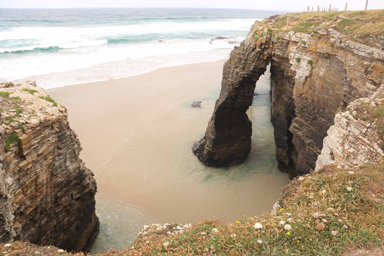Looking down at a couple of the sea arches at Praia As Catedrais from atop the sea cliffs