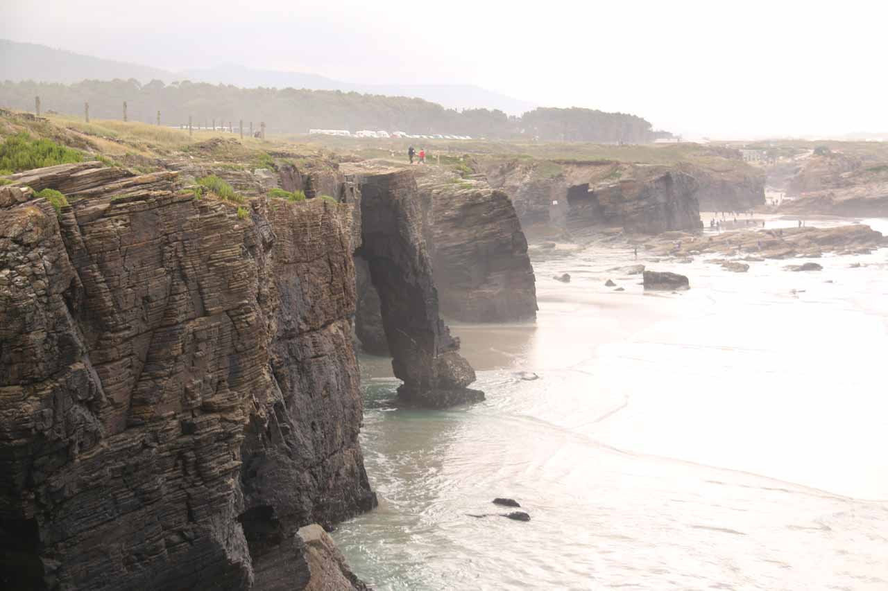 Looking along the sea cliffs of Praia As Catedrais in context with the ocean water still rippling below