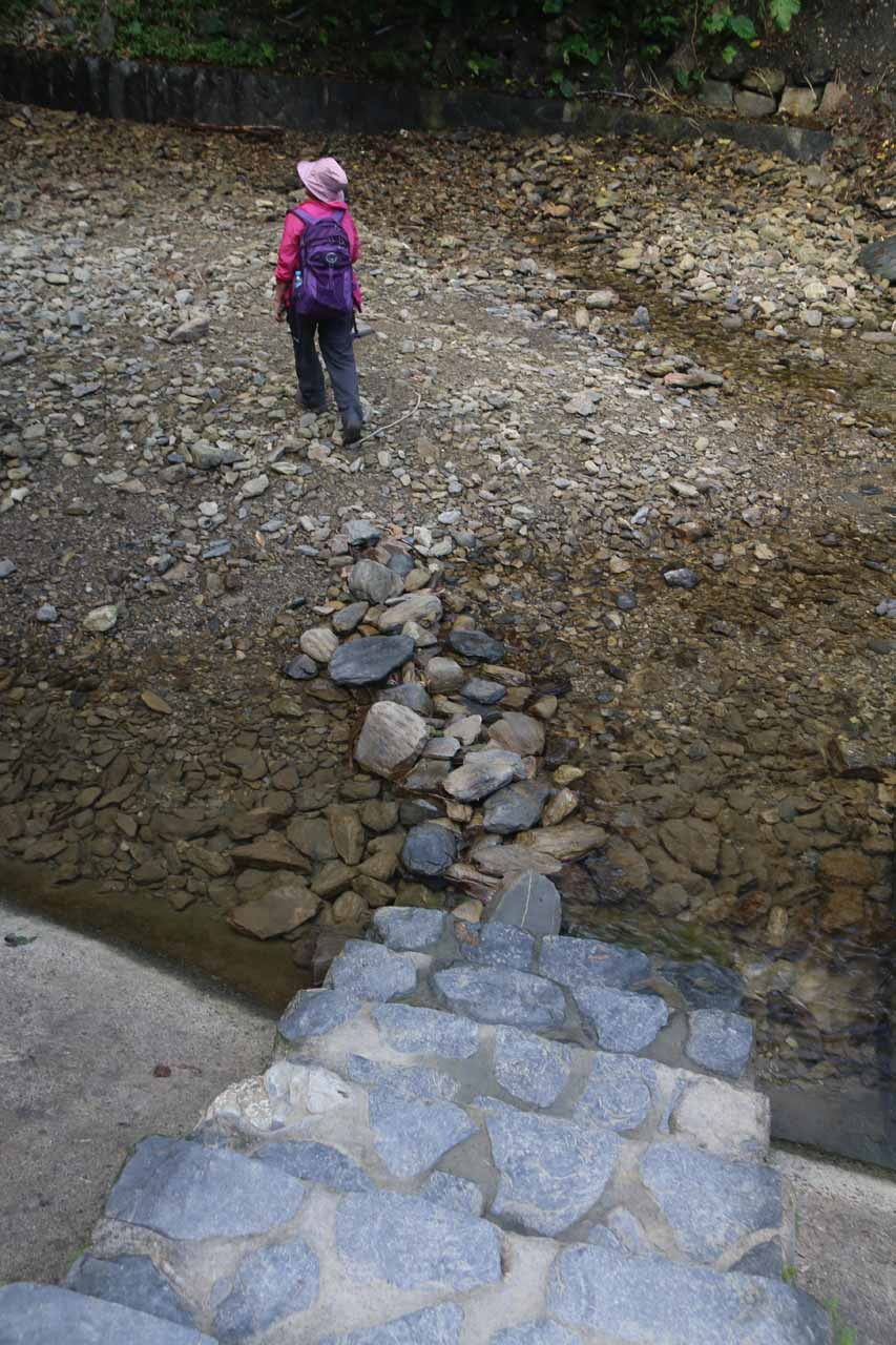 Mom walking down the steps onto the stream bed where we could scramble right up to the first Qingrengu Waterfall