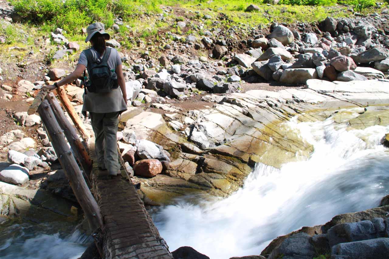 Julie crossing the one-sided log bridge before Van Trump Falls