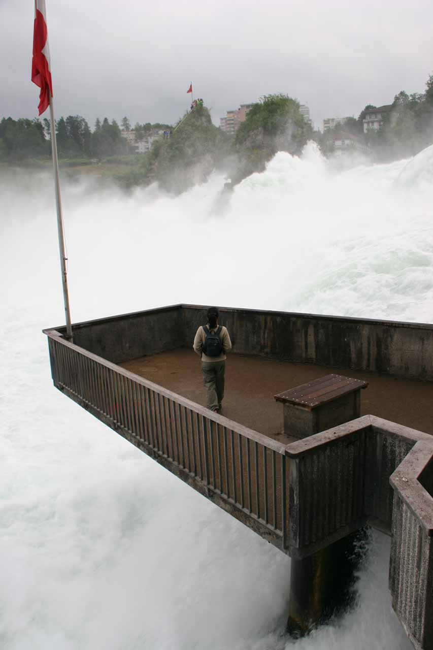 Julie walks onto the protruding platform perched dangerous within the base of Rhine Falls
