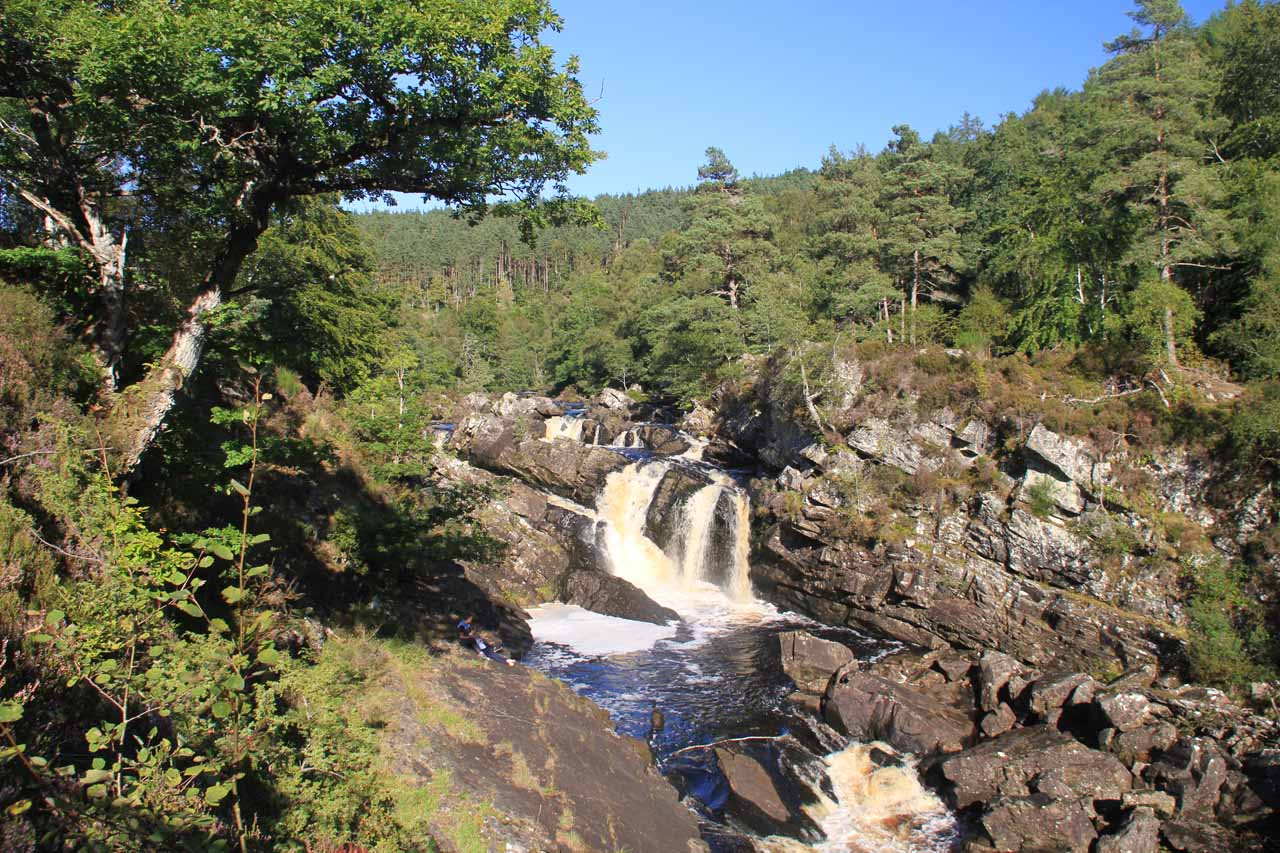 Angled contextual view of Rogie Falls from the near side of the suspension bridge