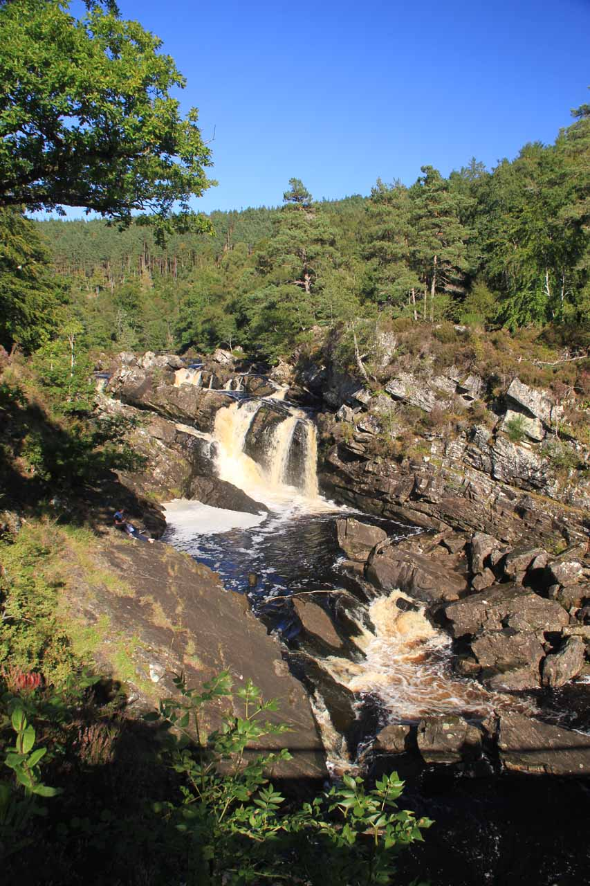 Portrait shot of Rogie Falls from the same spot revealing shadows from the suspension bridge