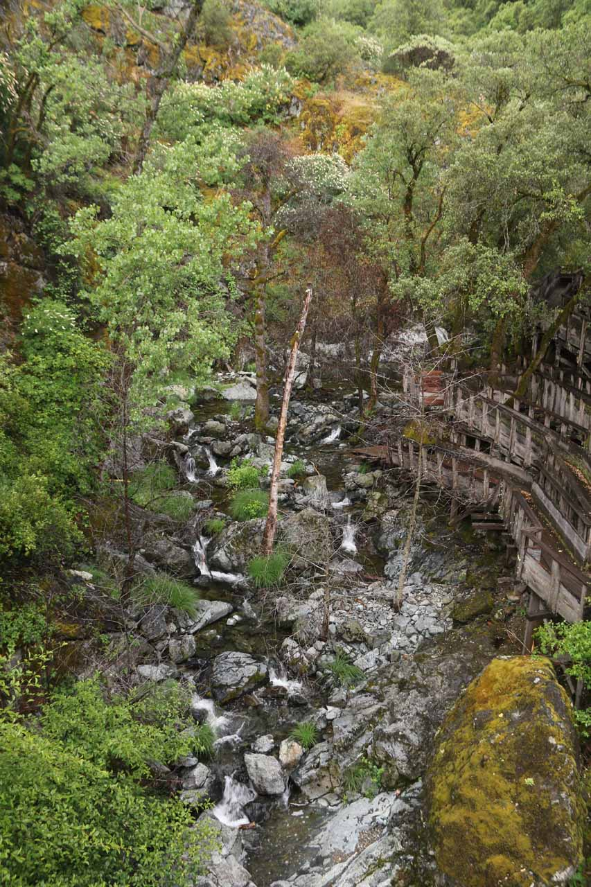 Looking upstream from the flume over Rush Creek towards smaller cascades and more wooden structures adjacent to them