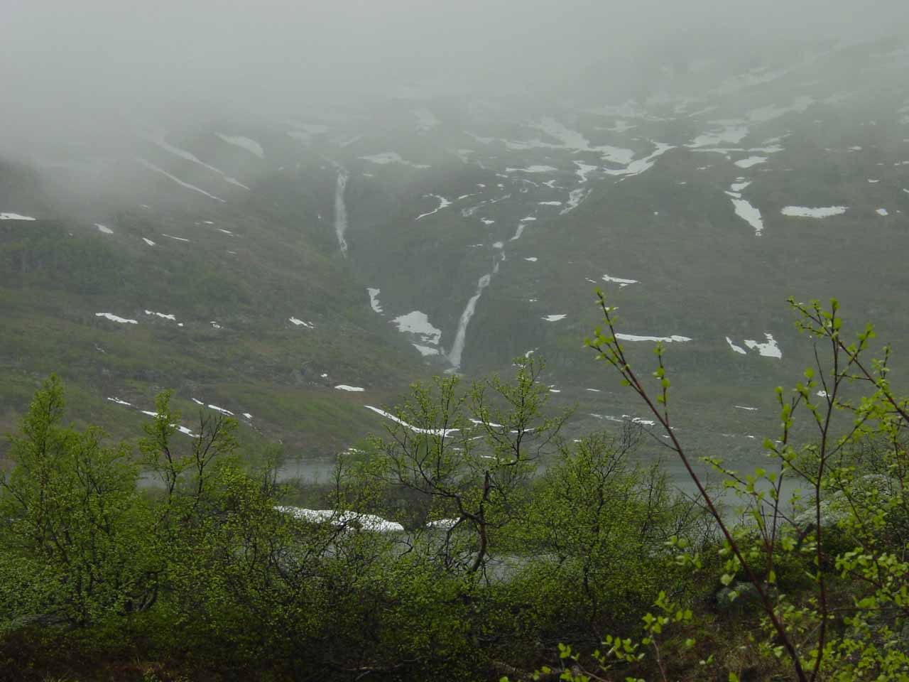 A pair of waterfalls amongst the snow shrouded in rain clouds