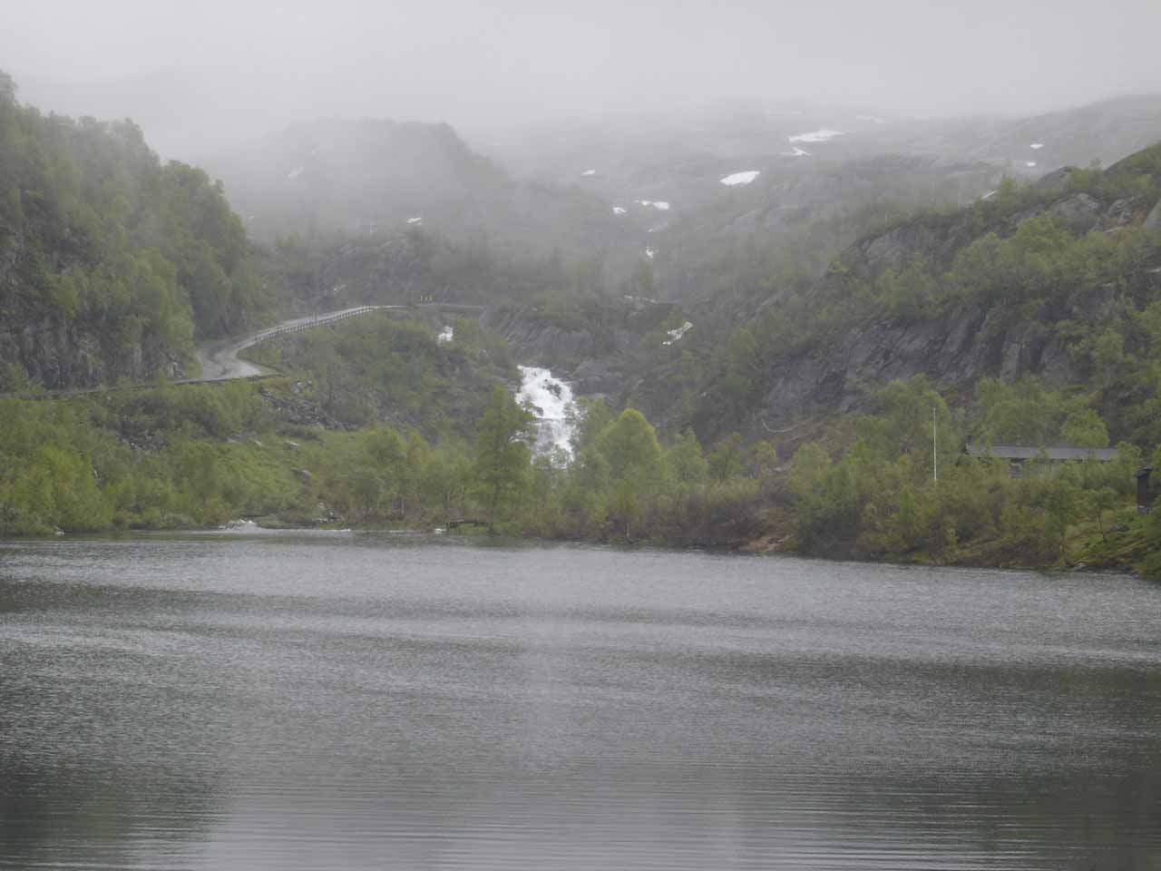 Looking across a moorish lake towards an attractive waterfall from just beneath the rain clouds