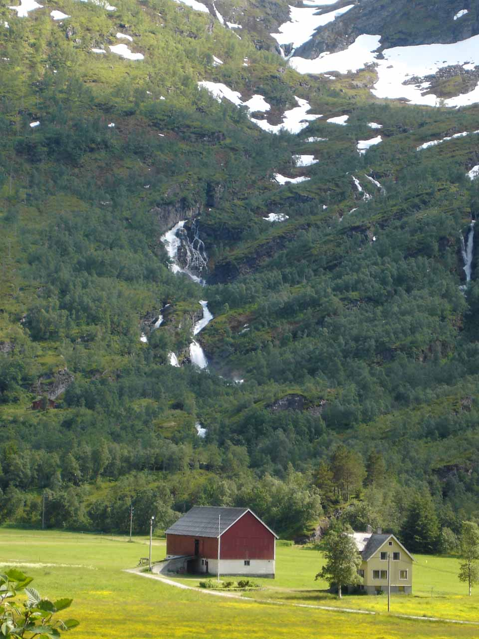 Looking towards some more mountain cascades fronted by cabins seen along Road 63 near Kvanndalsfossen