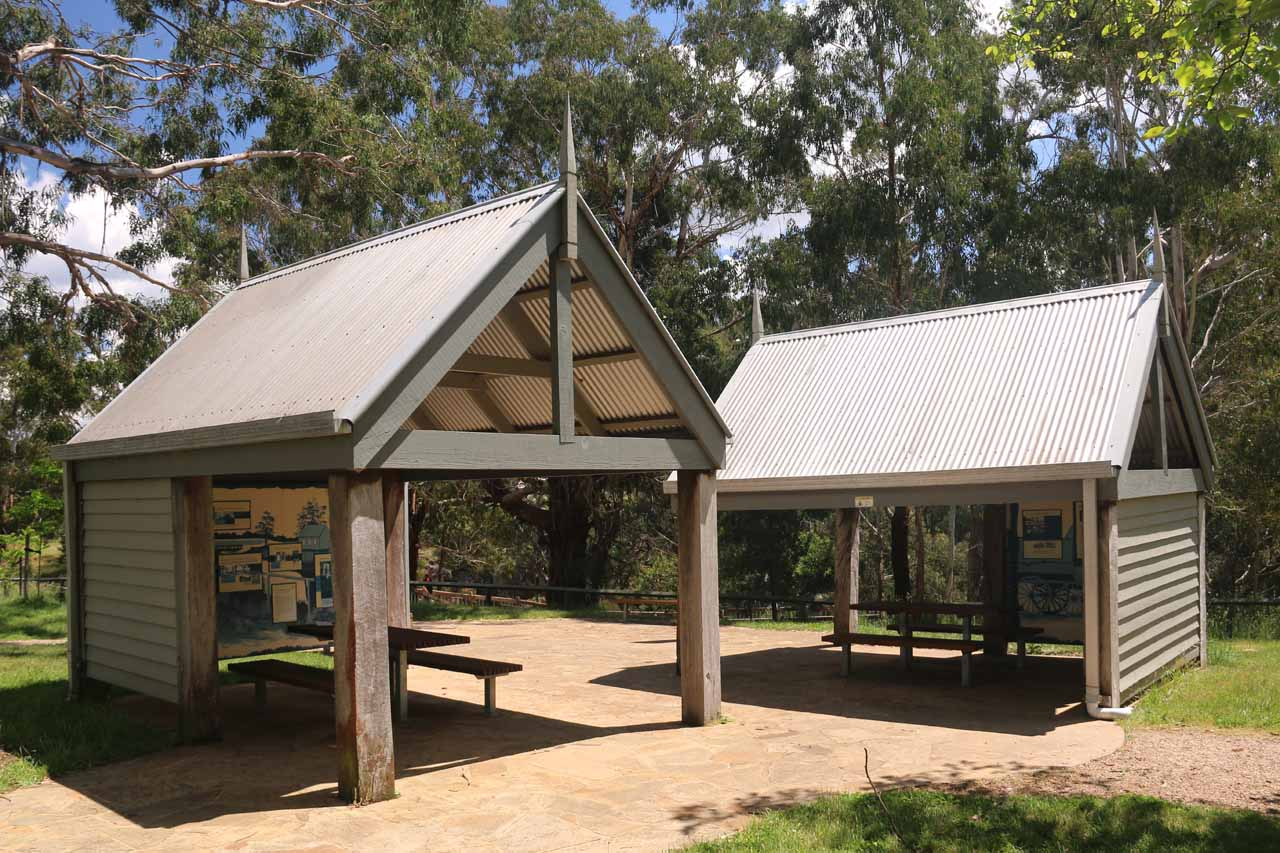 Interpretive signs depicting the history of the area amongst these shelters at the top of the gorge