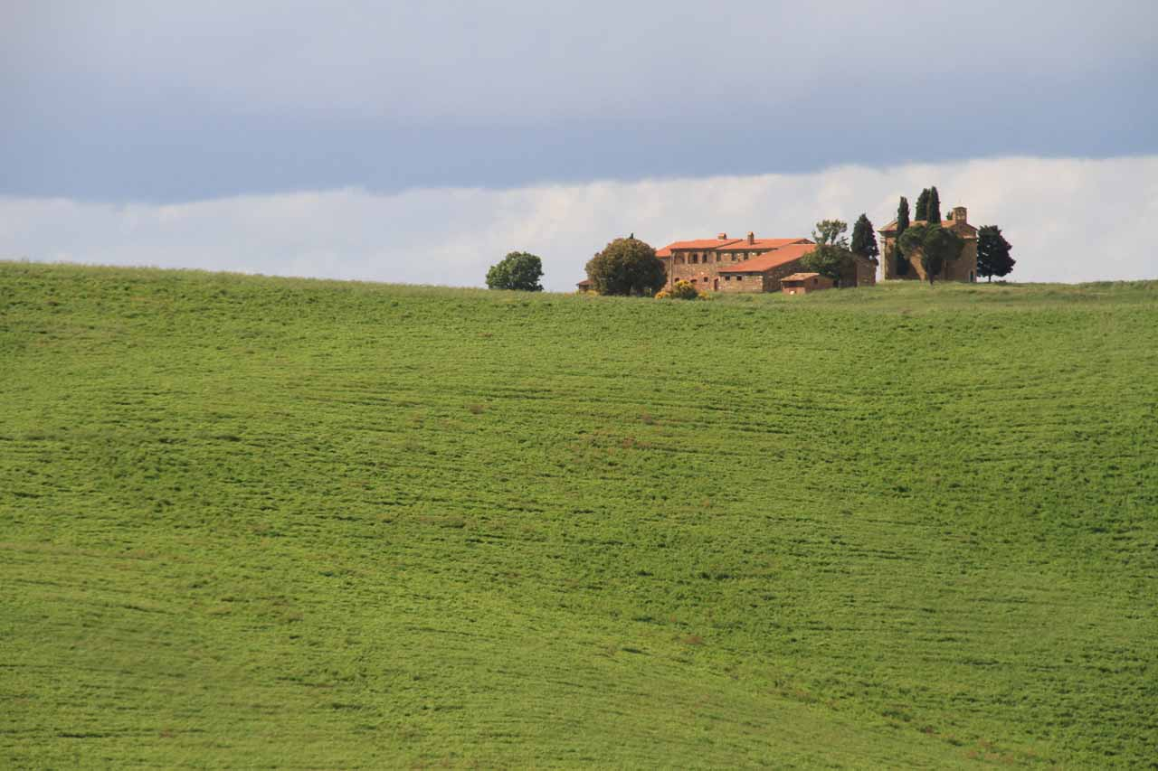 Looking towards another tuscan building surrounded by rolling green hills