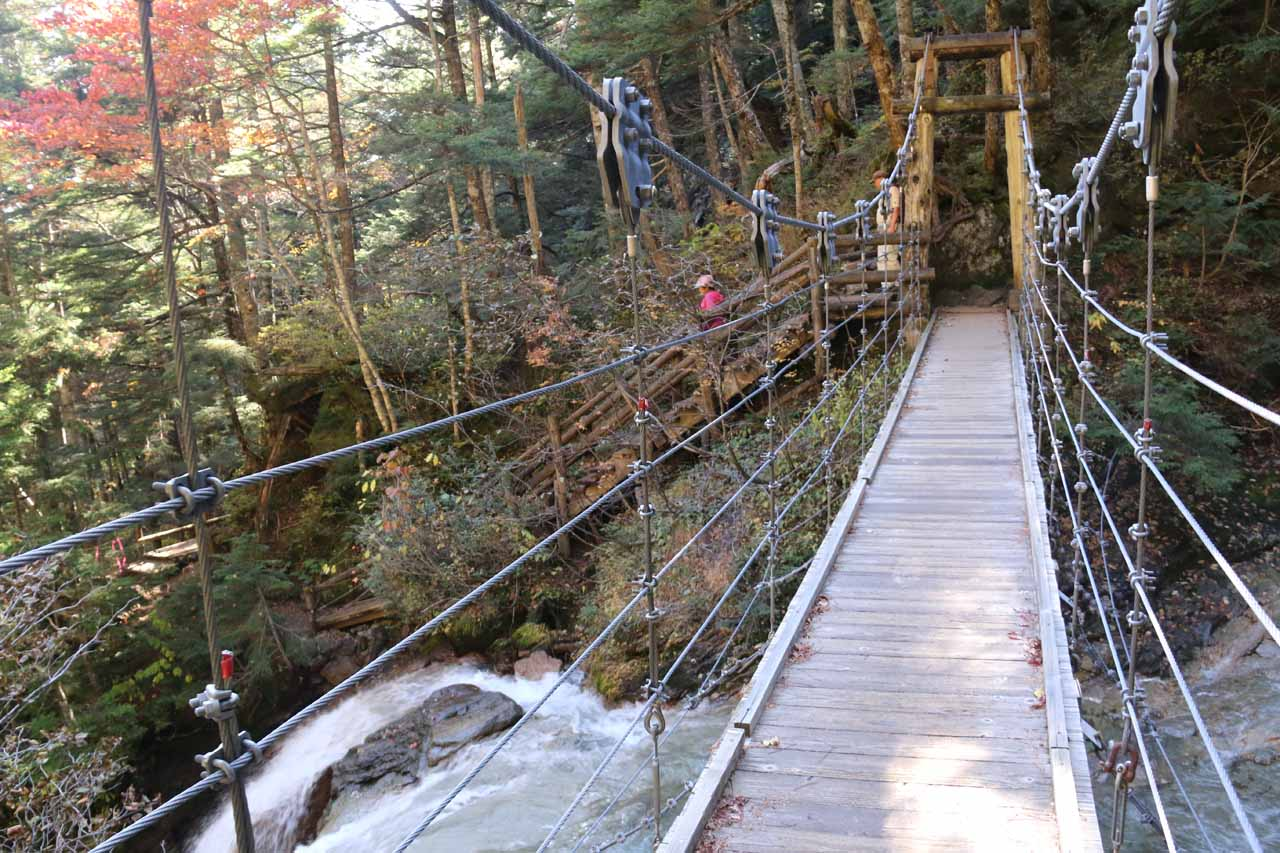 Crossing over the suspension bridge with an intermediate waterfall tumbling to the left