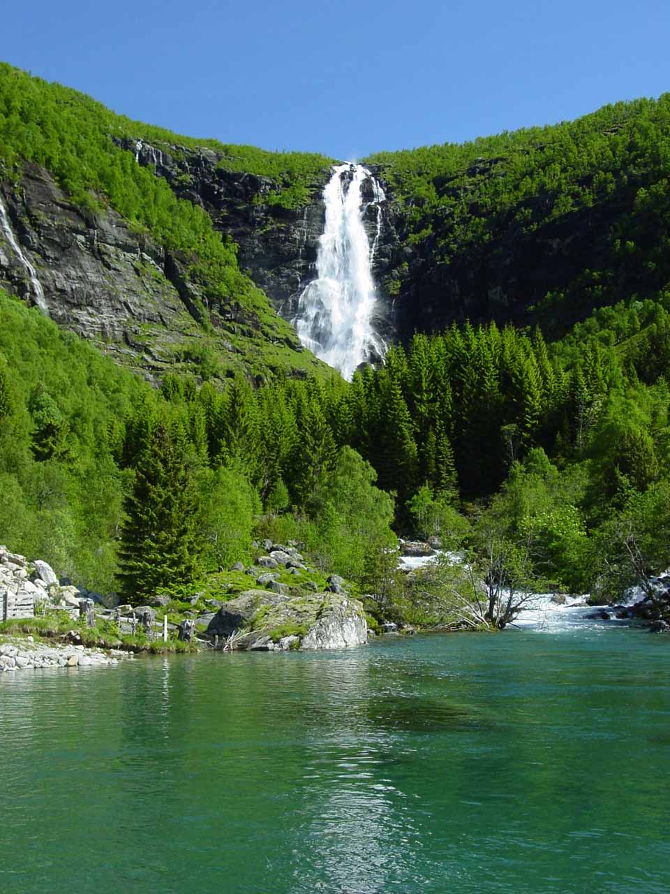 Closer look at Sanddalsfossen from across the clear man-made pool