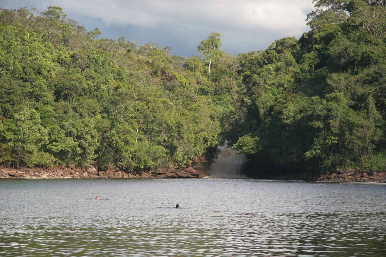 The hard-to-see Sapito Falls behind swimmers deep in the lagoon