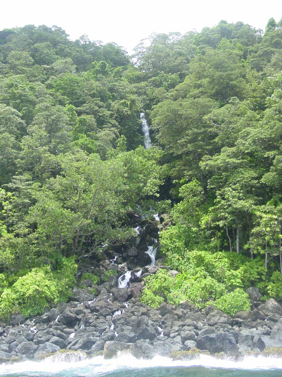 A taller waterfall hidden behind the dense foliage