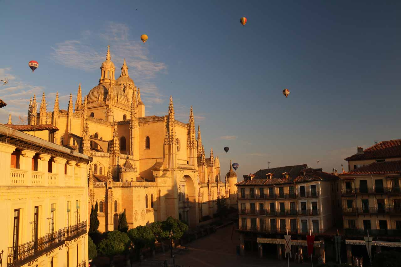 A series of hot air balloons hovering over the old town of Segovia