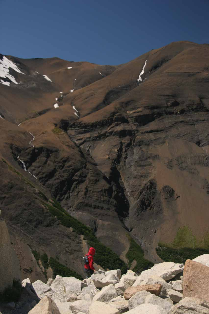 Julie starting to head back down with some volcanic-looking mountains and streaking cascades seen across the valley
