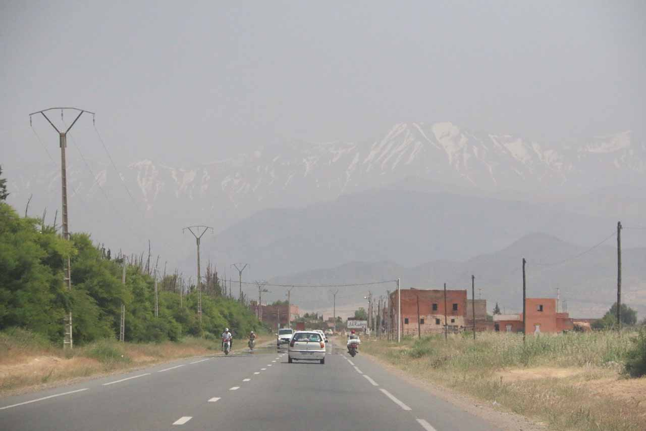Leaving Marrakech and driving towards Ourika Valley in the heart of the High Atlas Mountains seen here through the haze still clinging onto its snow despite the 40C weather