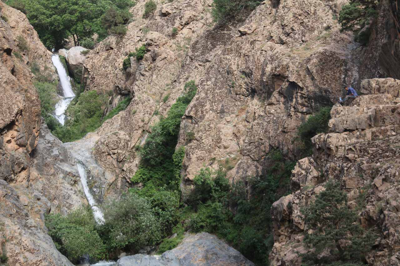 Context of a Berber local sitting on a cliff (right) checking out the Setti Fatma Waterfalls