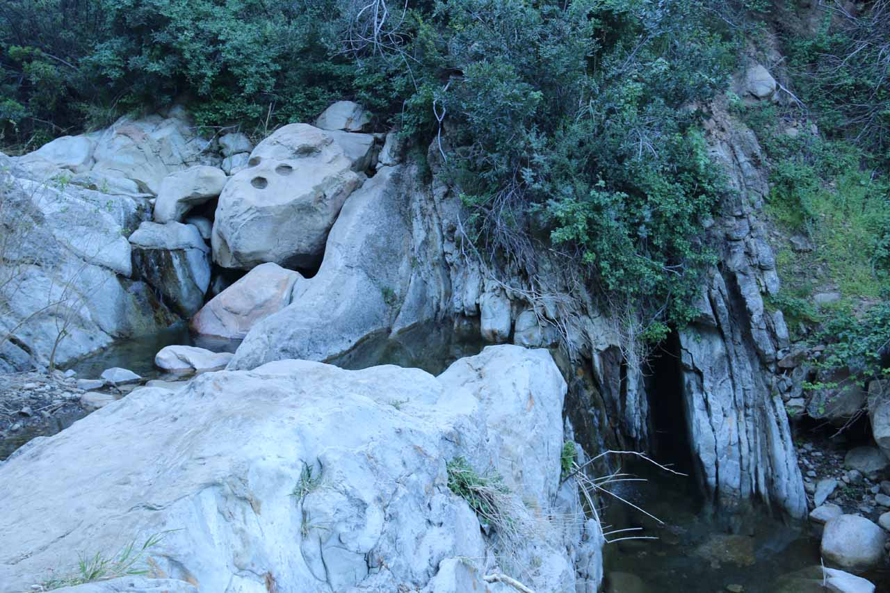 Looking towards a small pair of cascades near a potholed rock formation while scrambling towards Seven Falls
