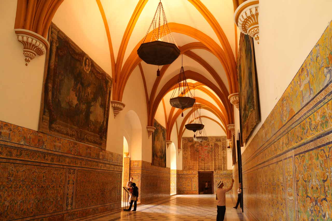 Walking within an elaborate hallway with tapestries and tiles flanking it