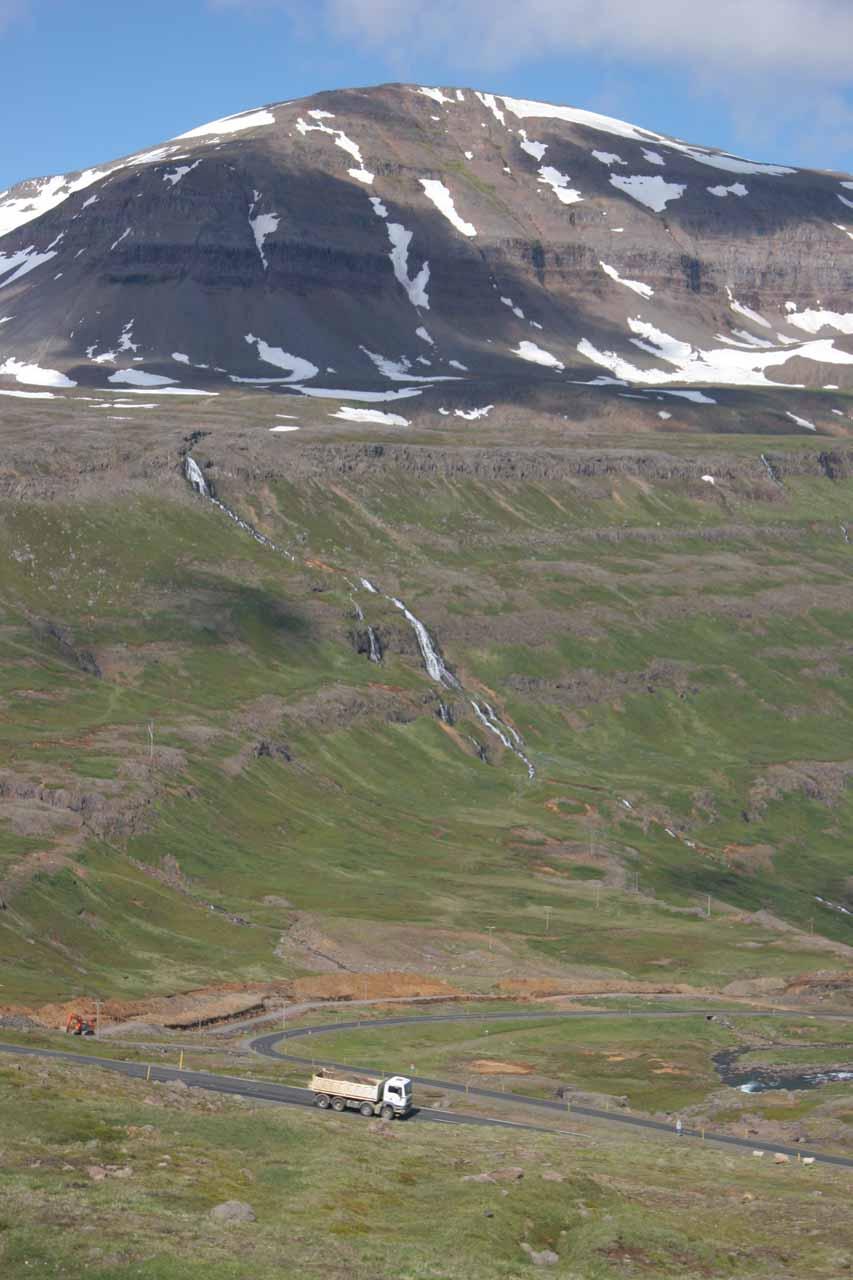 Long cascade tumbling beneath mountain with a truck providing scale