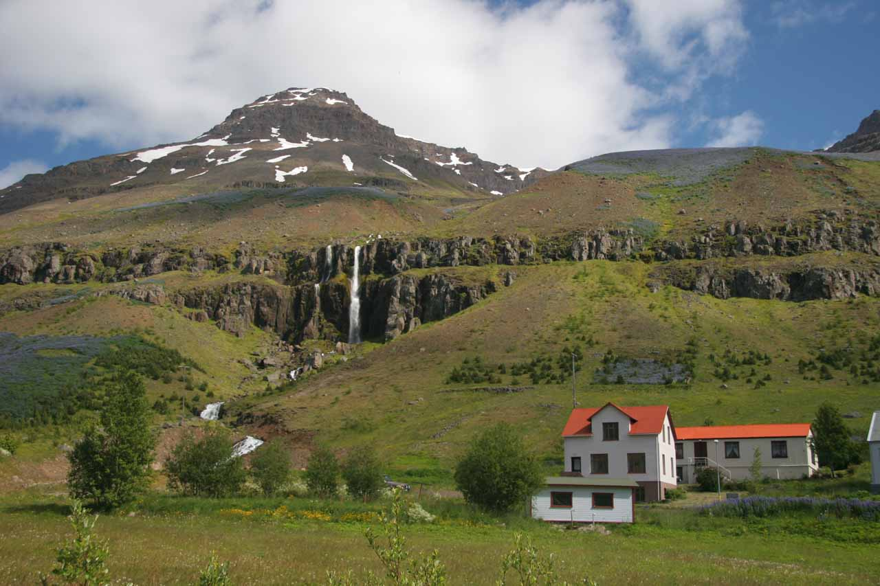 A waterfall behind someone's home in the town of Seyðisfjörður