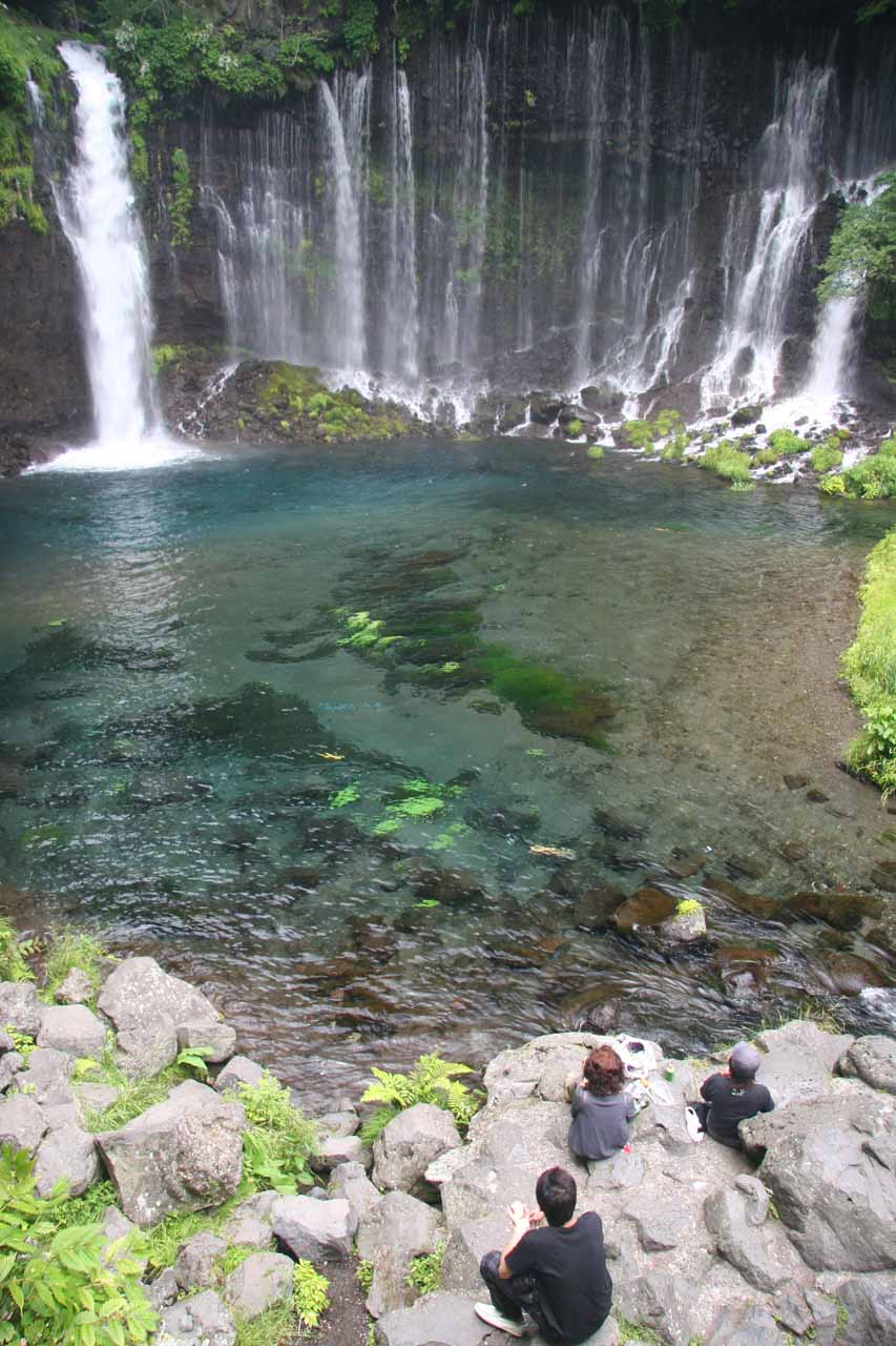 A family enjoys the Shiraito Waterfall along with its colorful plunge pool
