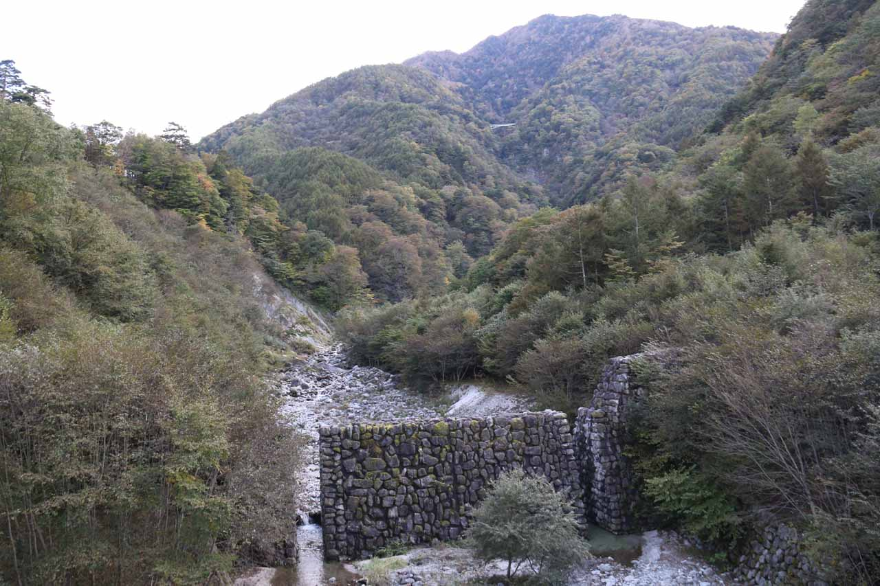 Looking upstream from the first suspension bridge towards a manmade wall with a pair of slits to allow the Ishiutoro River flow past