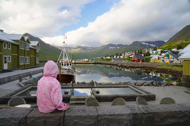 Siglufjordur_295_08142021 - Tahia checking out the harbor and reflections of the colorful Herring Era Museum and backing mountains in its waters at the scenic town of Siglufjörður, which was where we were headed after making the unexpected stop for Migandifoss