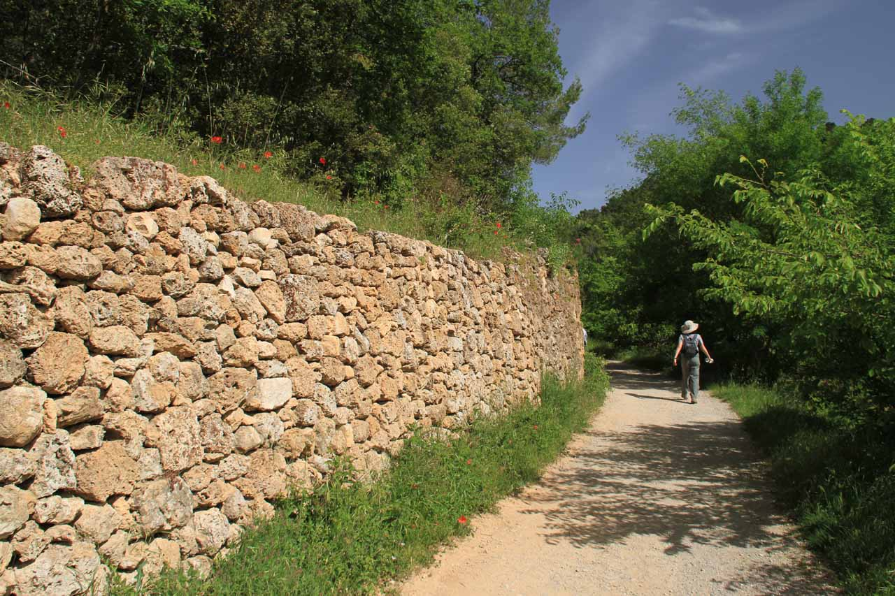 An ancient-looking wall flanking the trail