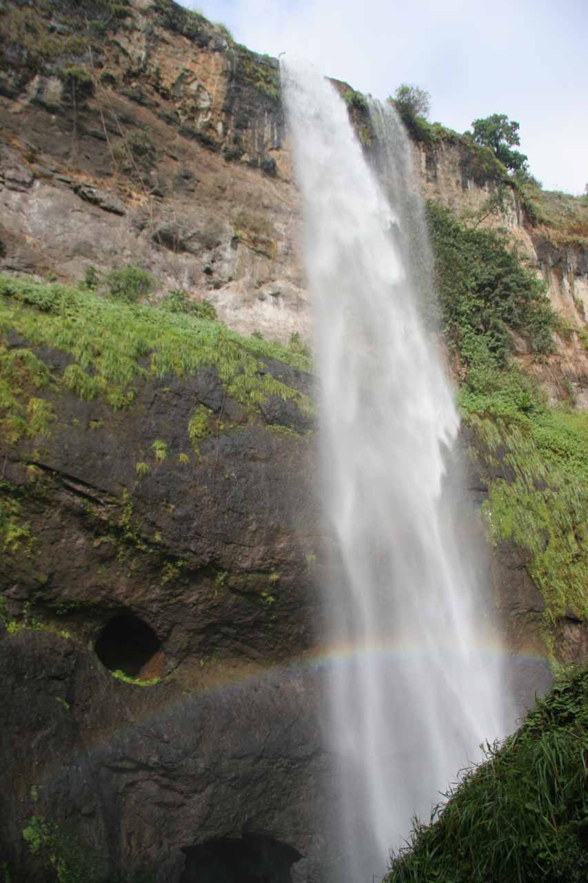 At the misty base of the third Sipi Falls accompanied by a faint rainbow