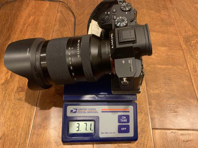 The Sony SEL24240 FE 24-240mm f/3.5-6.3 OSS Lens sitting on a postal scale