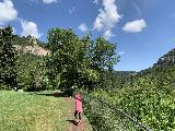 Spearfish_Canyon_015_iPhone_07302020 - Tahia following the trail along the fence leading towards an overlook and the continuation of the trail going to the base of Spearfish Falls
