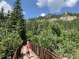Spearfish_Canyon_099_iPhone_07302020 - Julie and Tahia going back across the footbridge over Spearfish Creek as we were returning from Spearfish Falls