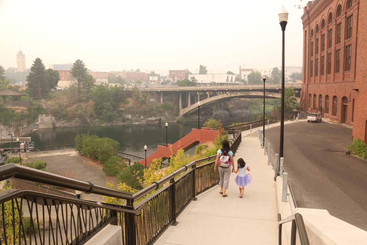 Julie and Tahia walking towards the Monroe Street Dam behind the Huntington Park building
