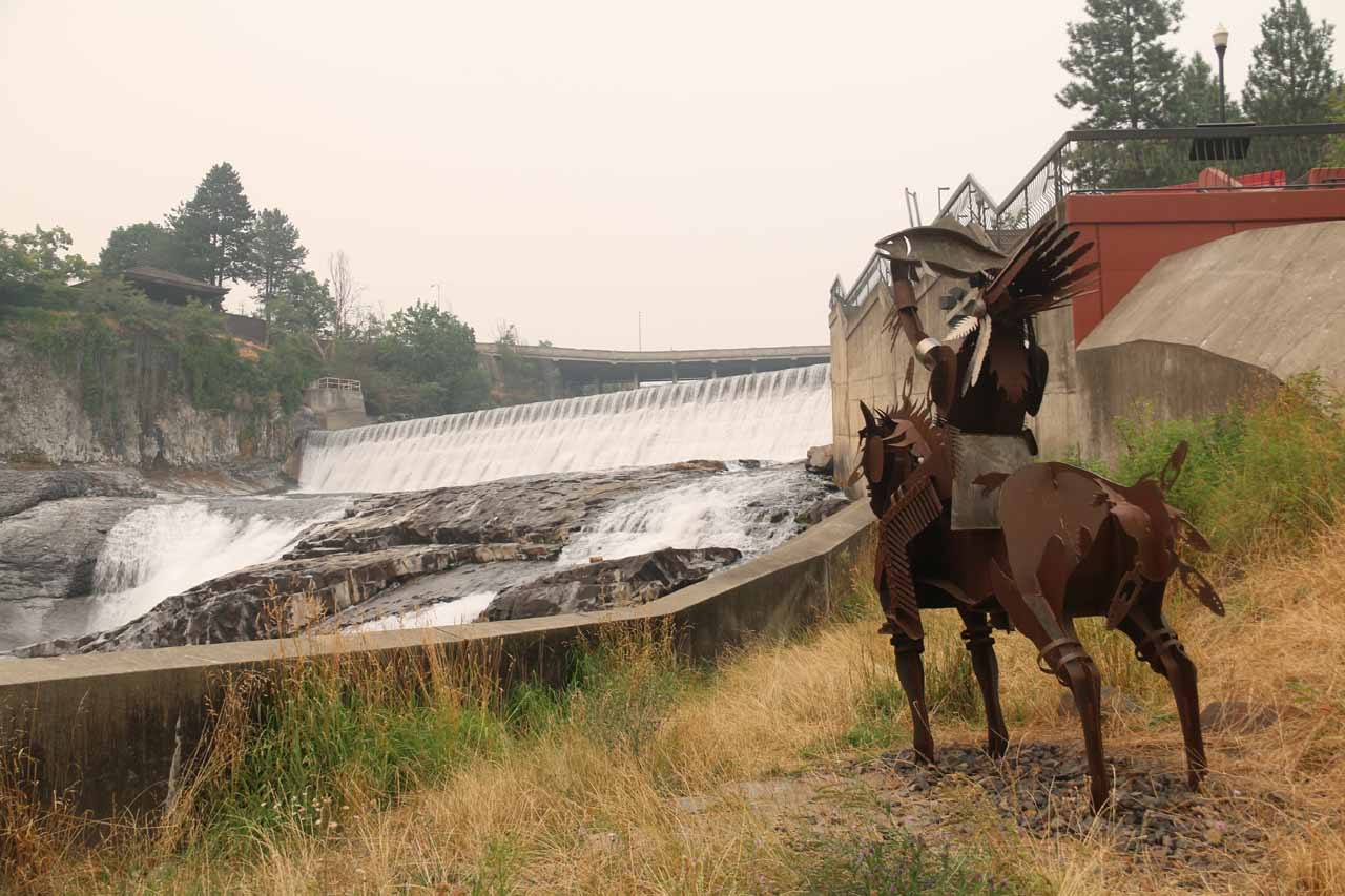 Context of some metal sculpture or statue of a Native American on horseback and the Lower Spokane Falls