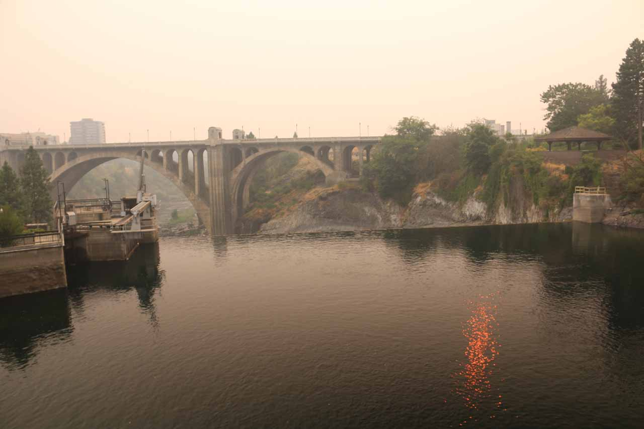 Looking downstream over the brink of the Lower Spokane Falls with the eerie red glow from the smoke-obscured sun shining in the Spokane River